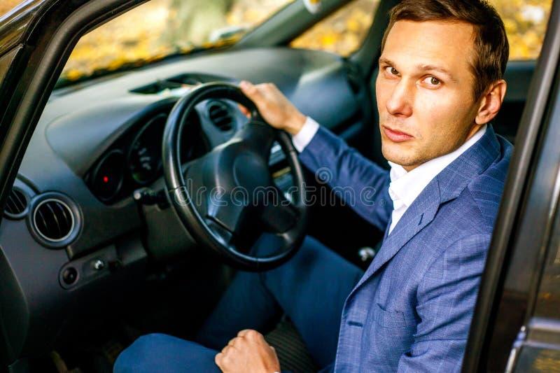Knappe succesvolle mens in kostuumzitting in smartphone van de autoholding en het glimlachen stock afbeeldingen