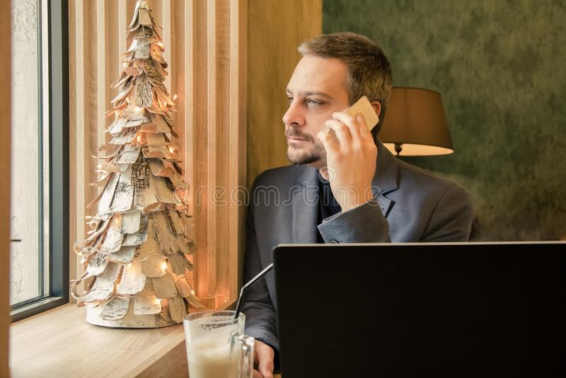 Knappe succesvolle zakenman die op mobiele telefoon spreken, die l gebruiken stock fotografie