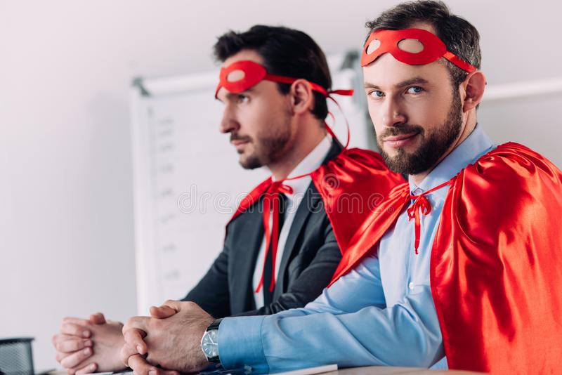 knappe super zakenlieden in maskers en kaap die bij lijst zitten stock fotografie
