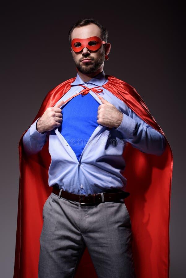knappe super zakenman in masker en kaap die blauw overhemd tonen stock afbeeldingen