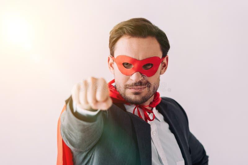 knappe super zakenman in masker en kaap die vuist tonen stock fotografie