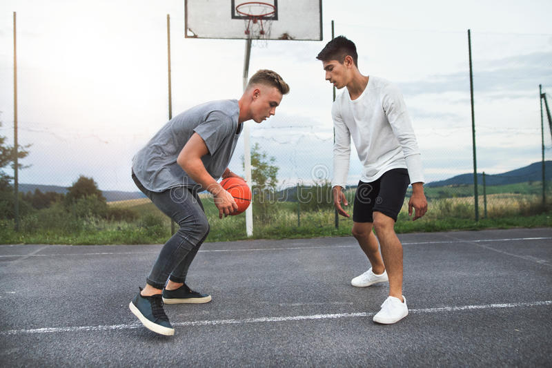 Knappe tieners die basketbal in openlucht op speelplaats spelen royalty-vrije stock afbeeldingen