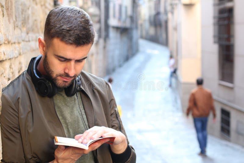 Knappe toerist die een gids raadplegen tijdens een reis rond Europa stock foto's