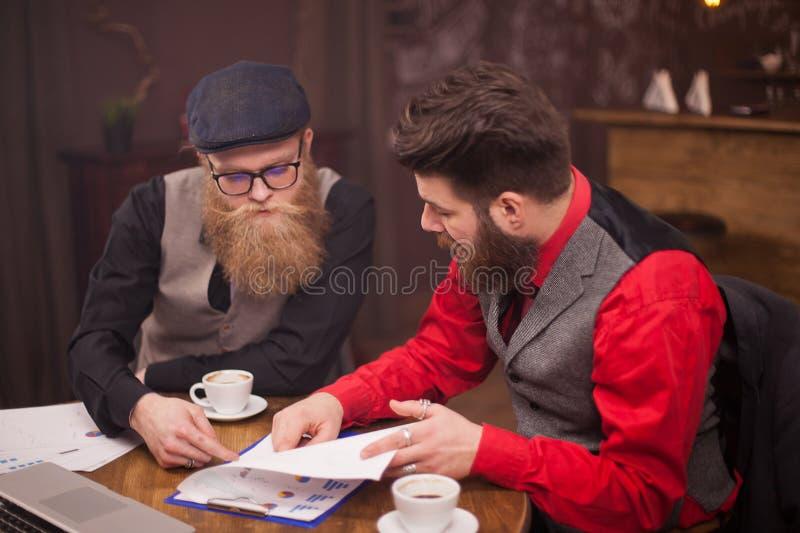Knappe twee zakenlieden die een vergadering in een koffiewinkel hebben stock foto's