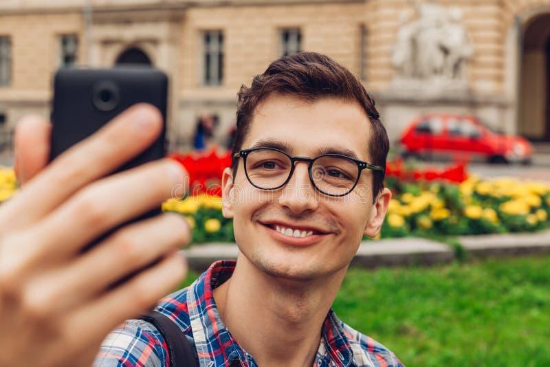 Knappe universiteitsmens die selfie in het park van de de lentecampus nemen Gelukkige kerelstudent die glazen dragen tegen univer stock afbeelding