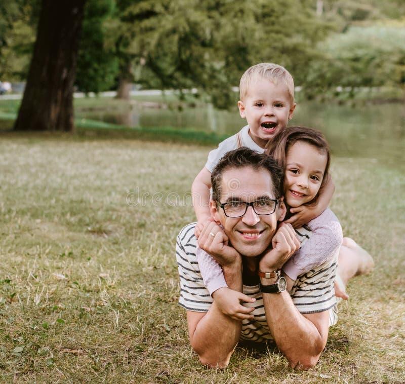 Knappe vader met zijn geliefde kinderen die in het park rusten stock foto