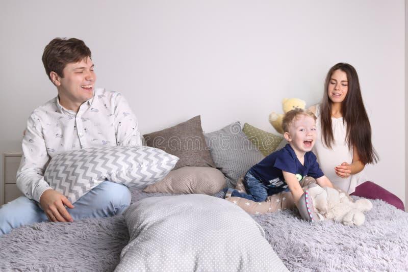 Knappe vader, moeder, weinig leuk zoonsspel op bed stock afbeelding