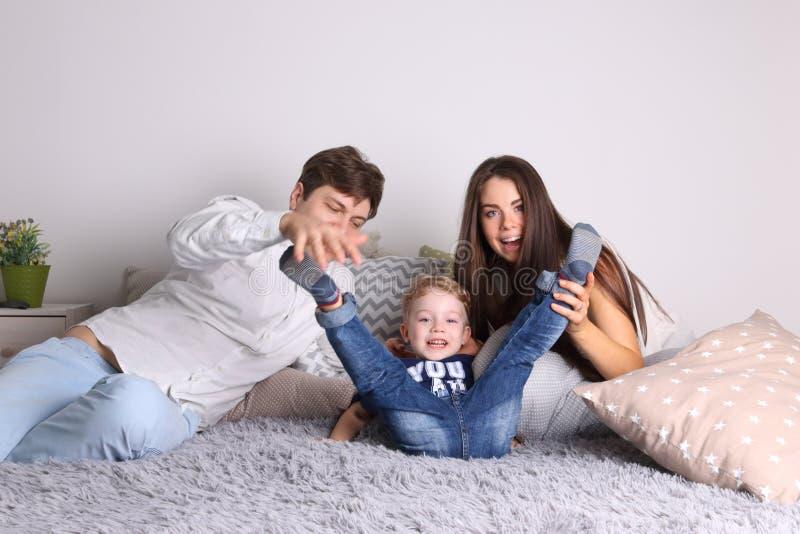 Knappe vader, moeder, weinig leuk zoonsspel op bed royalty-vrije stock foto's