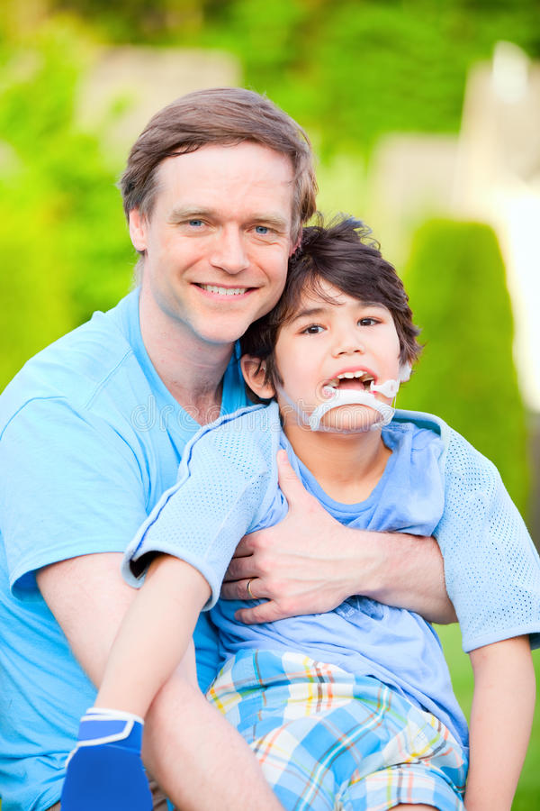 Knappe vaderholding die gehandicapte zoon in openlucht glimlachen stock fotografie