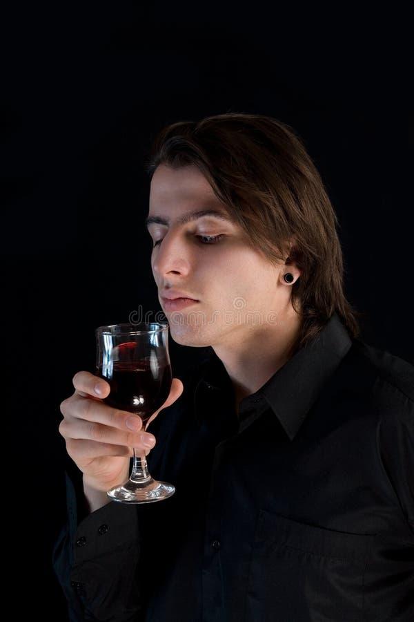 Knappe vampier met glas wijn of bloed stock afbeelding
