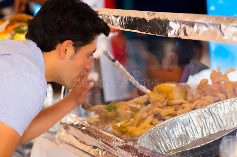 Knappe verraste jonge mens die op een heerlijk Ecuatoriaans traditioneel typisch Andesvoedsel letten stock fotografie