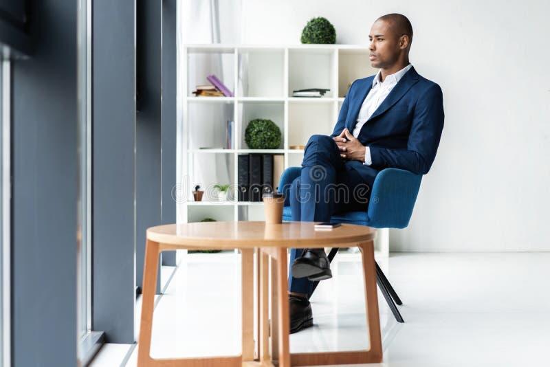 Knappe vrolijke Afrikaanse Amerikaanse uitvoerende bedrijfsmens op het werkruimtekantoor royalty-vrije stock afbeelding