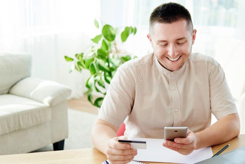 Knappe vrolijke mens die met creditcard op smartphone thuis bureau betalen, exemplaarruimte Technologie, bankwezen, zaken, online royalty-vrije stock foto