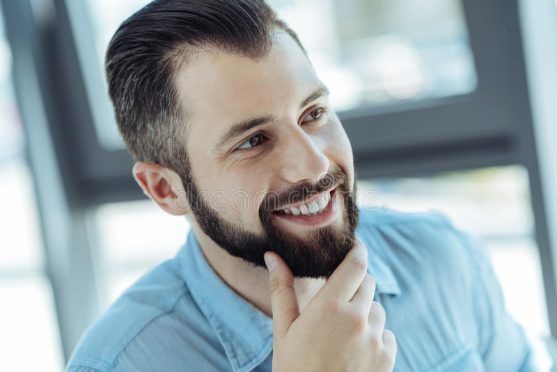 Knappe vrolijke mens die zijn kin strijken royalty-vrije stock afbeelding