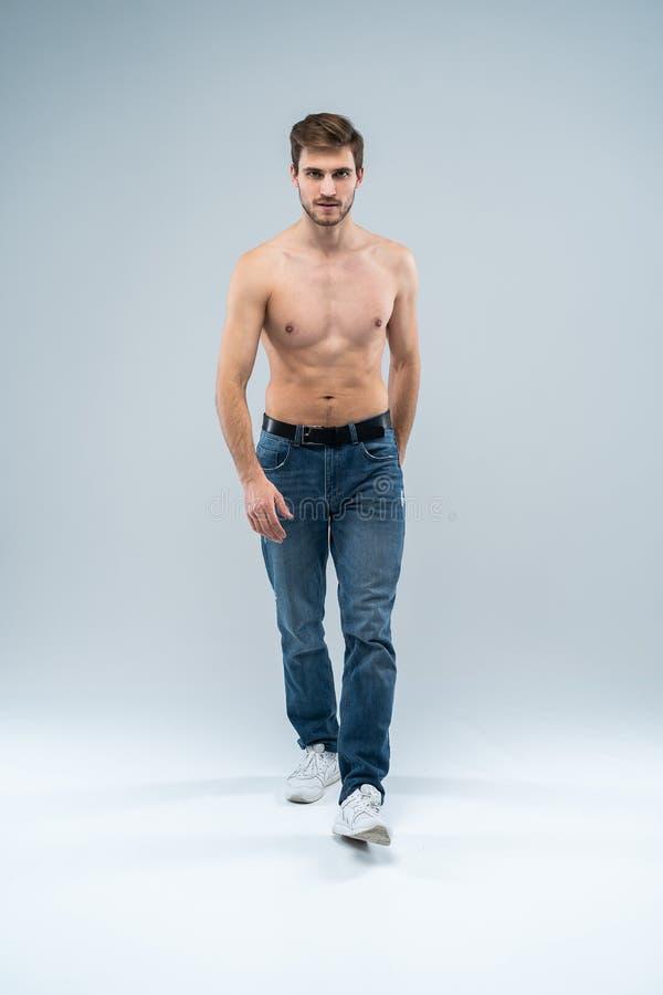 Knappe vrolijke mens Volledige lengte van de knappe jonge shirtless mens die in jeans camera met glimlach bekijkt terwijl status stock afbeelding