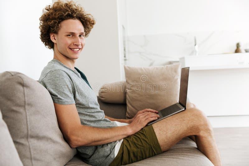 Knappe vrolijke mensenzitting bij bank die laptop computer met behulp van stock afbeelding