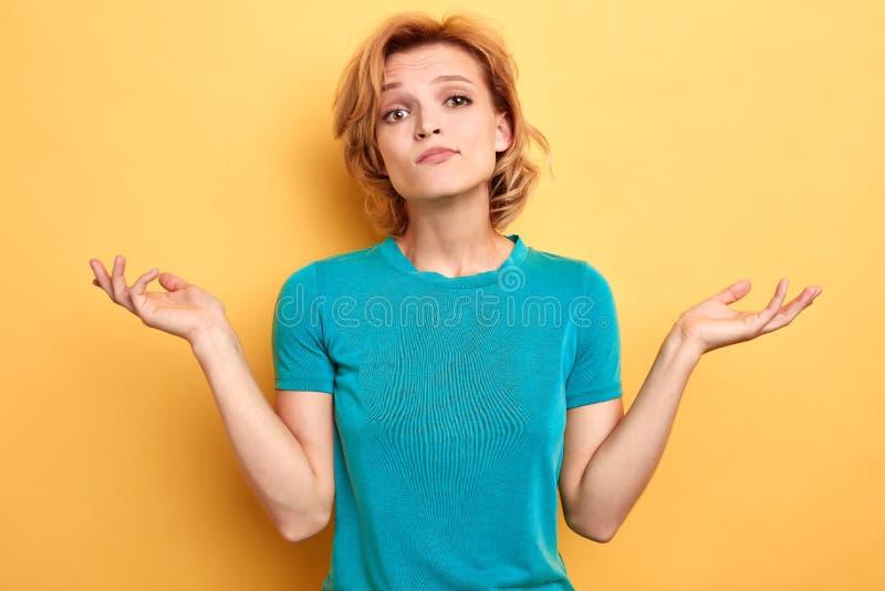 Knappe vrouw in blauwe T-shirt met open palmen die aan de camera poing stock afbeeldingen