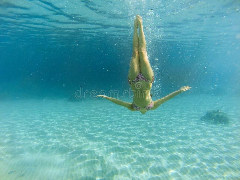 Knappe vrouw die onder het overzees duiken royalty-vrije stock afbeeldingen