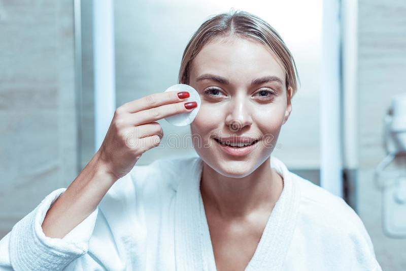 Knappe vrouw met zacht glimlach schoonmakend gezicht met doorweekt katoenen stootkussen royalty-vrije stock foto's