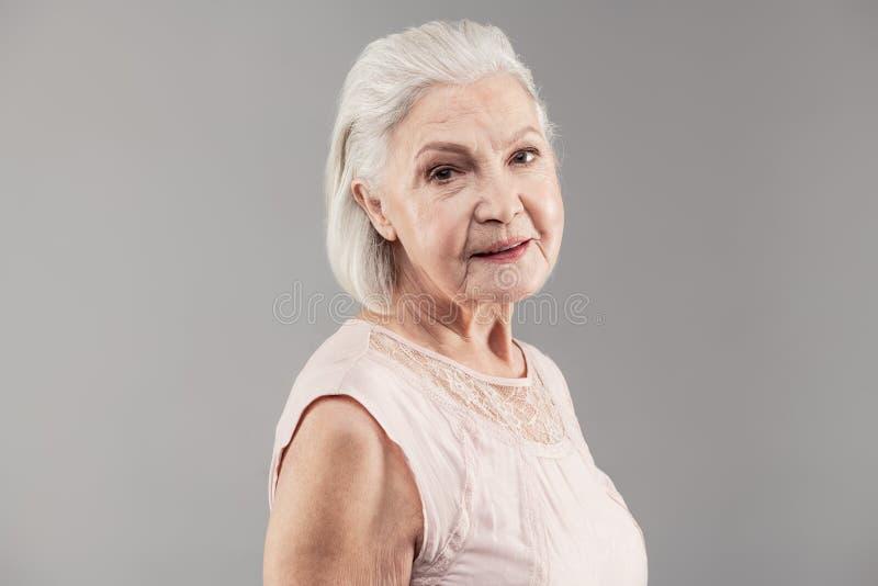 Knappe vrouwelijke gepensioneerde die lichte sleeveless blouse dragen stock afbeeldingen