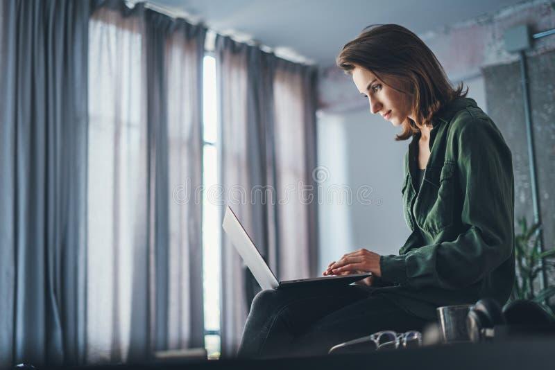 Knappe vrouwelijke medewerkerzitting bij de lijst en het gebruiken van laptop computer Het werk proces bij het coworking van stud royalty-vrije stock foto's