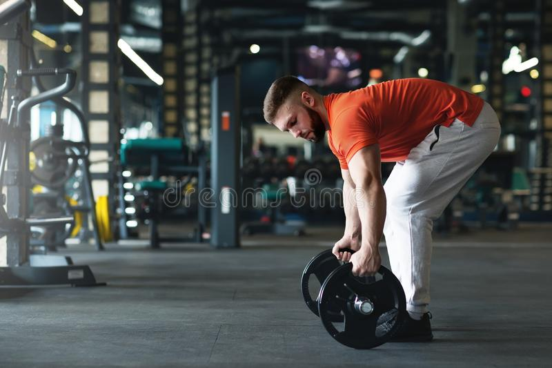Knappe weightlifter die voor opleiding in gymnastiek voorbereidingen treffen stock afbeeldingen