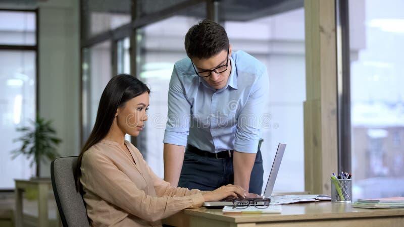 Knappe werkgever die het werk van vrouwelijke medewerker, journalisten controleren die artikel schrijven royalty-vrije stock afbeeldingen
