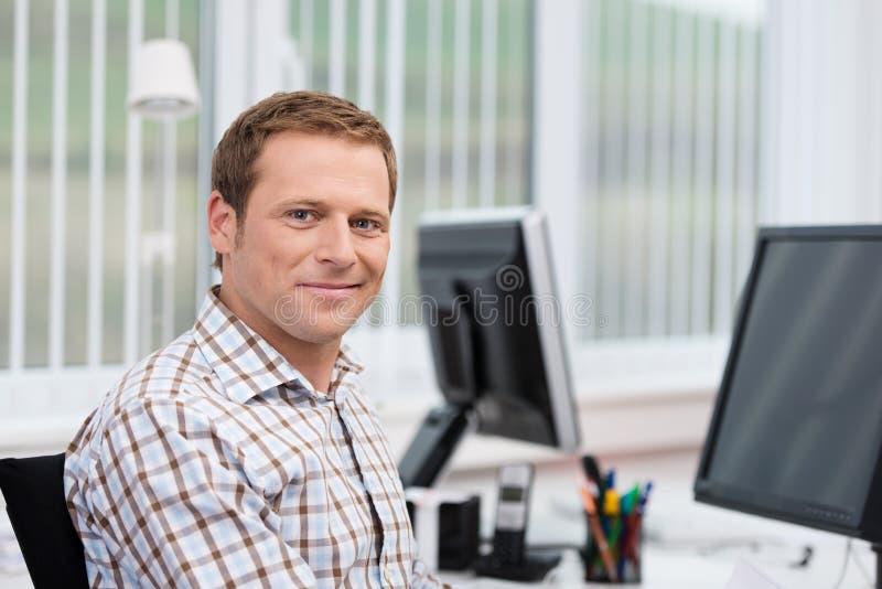 Knappe zakenman bij zijn bureau stock afbeeldingen