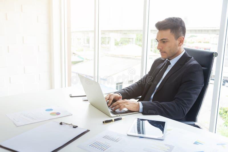 Knappe zakenman die bij bureau met laptop en document grafiek in bureau werken Professioneel zakenman en technologieconcept royalty-vrije stock foto's