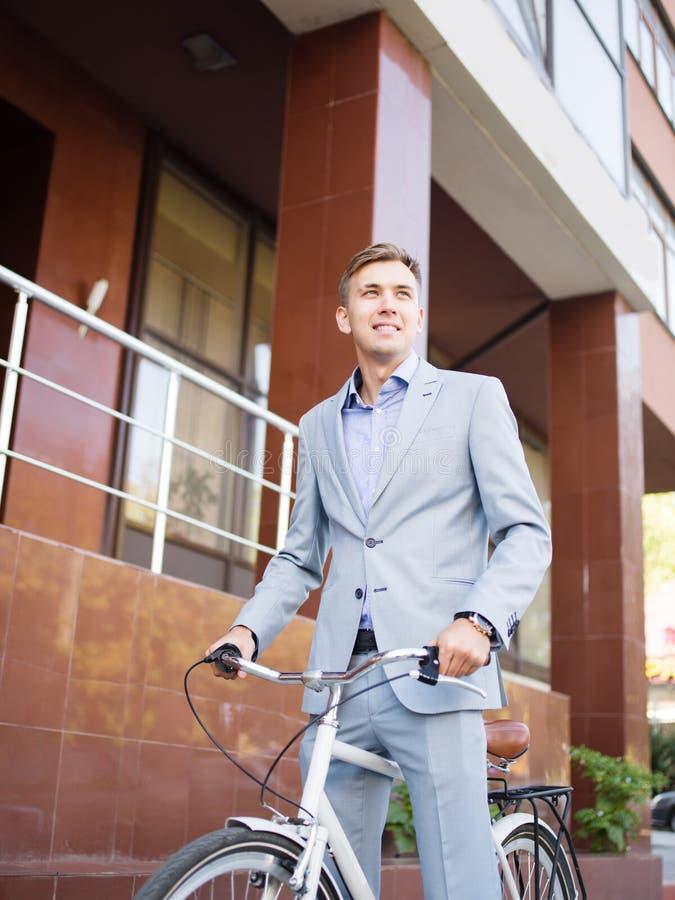 Knappe zakenman die een fiets berijden op de stedelijke achtergrond Gezond levensstijlconcept De ruimte van het exemplaar royalty-vrije stock afbeelding