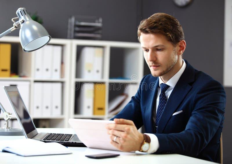 Knappe zakenman die met laptop werken stock foto's