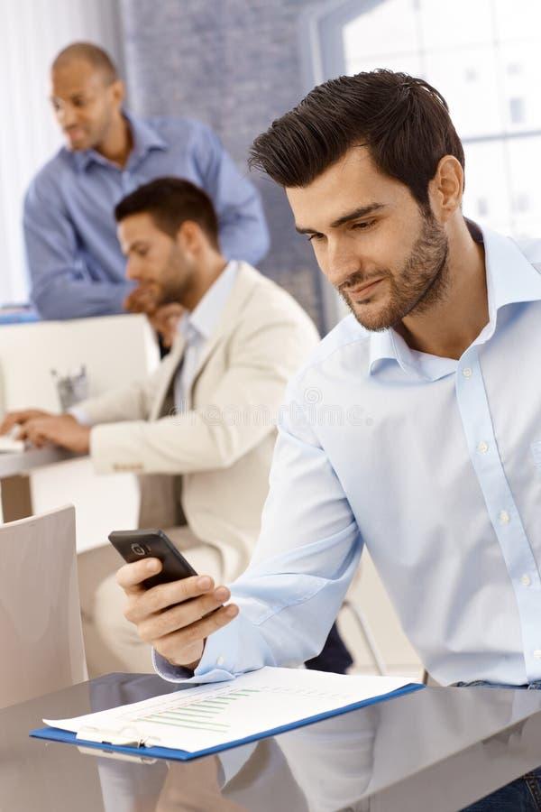 Knappe zakenman die mobilofoon met behulp van stock foto's