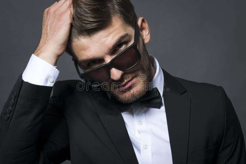 Knappe zakenman die zijn band aanpast stock foto's