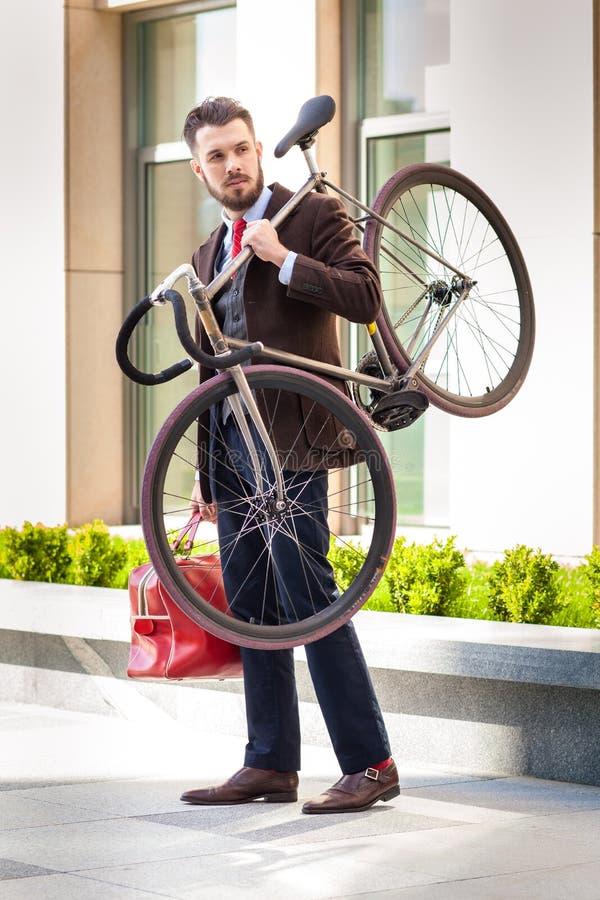 Knappe zakenman die zijn fiets in van hem dragen stock afbeeldingen