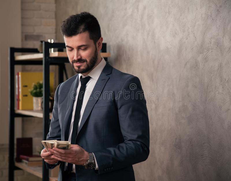 Knappe knappe zakenman in het bureau die zich door zijn bureau en tellend geld bevinden het dragen van kostuum en een band royalty-vrije stock foto