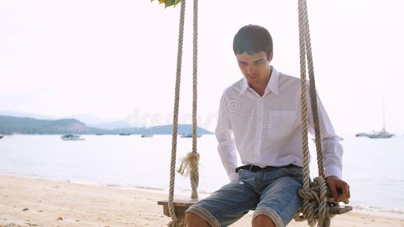 Knappe zakenman in wit overhemd die op hangmat op exotisch tropisch strand slingeren stock foto's