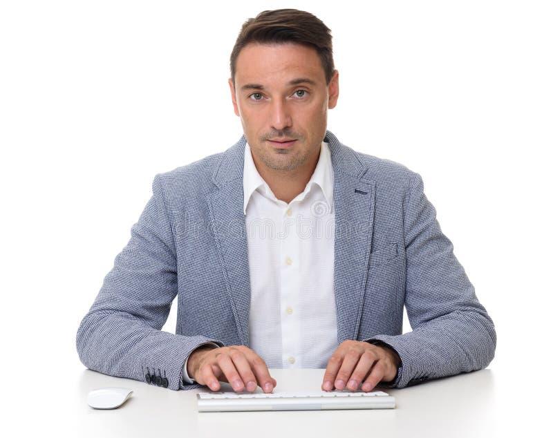 Knappe zakenmanzitting bij bureau, die aan computer werken royalty-vrije stock afbeeldingen
