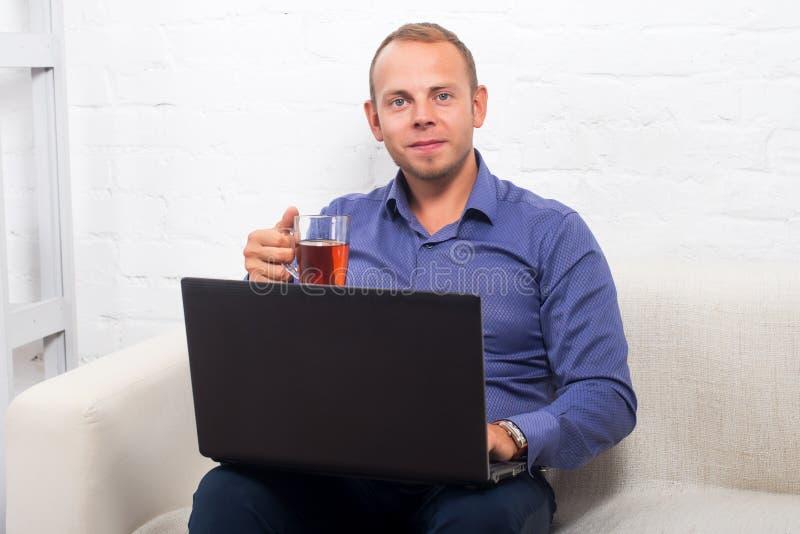 Knappe zakenmanzitting op laag met laptop thuis in de woonkamer, die camera kijken stock fotografie