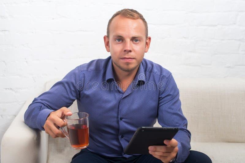 Knappe zakenmanzitting op laag met laptop thuis in de woonkamer, die camera kijken royalty-vrije stock foto's