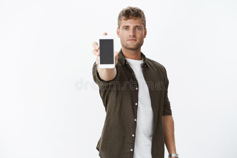 Knappe zekere blonde mens die u het smartphonescherm tonen die hand met mobiele telefoon uitbreiden bij camera die koel kijken en royalty-vrije stock afbeelding