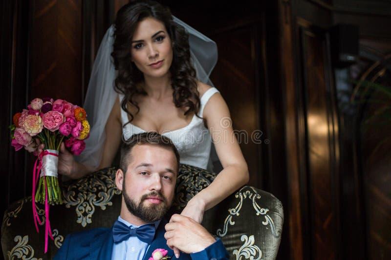 Knappe zekere bruidegom en mooie donkerbruine bruid met bouqu stock foto's