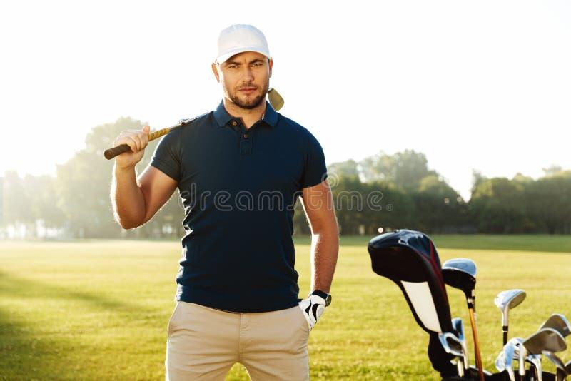 Knappe zekere mannelijke golfspeler die zich met golfclub bevinden royalty-vrije stock foto