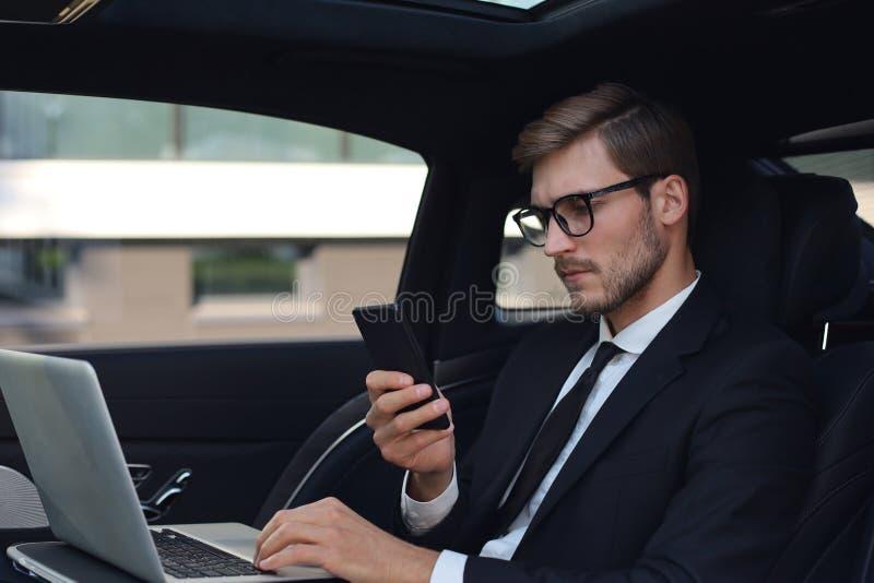 Knappe zekere mens die in volledig kostuum zijn smartphone bekijken terwijl het zitten in de auto en het gebruiken van laptop stock foto's