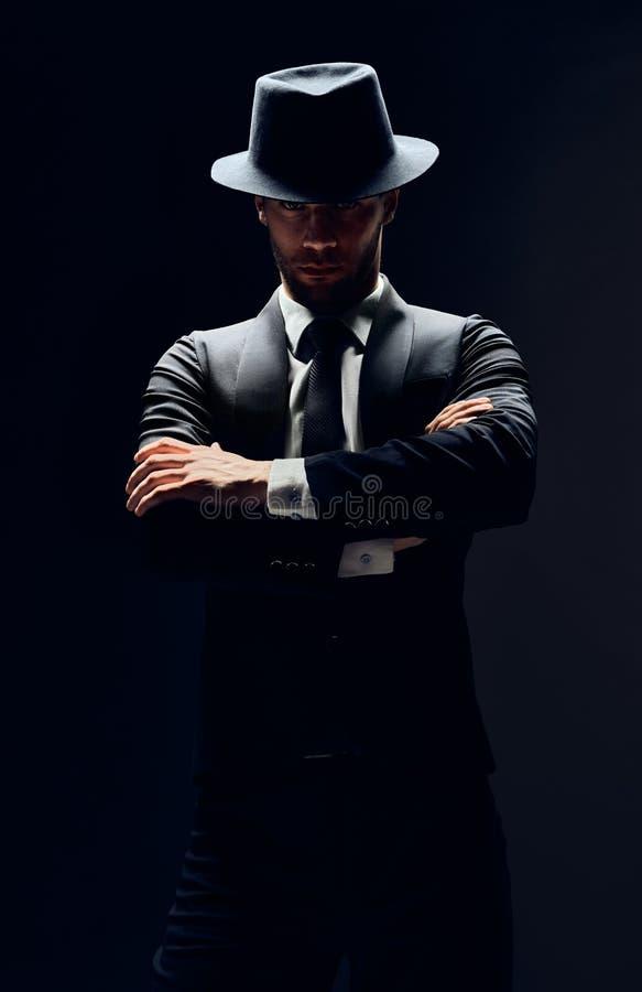 Knappe zekere mens in zwart die kostuum en hoed met wapens op donkere achtergrond worden gekruist stock fotografie
