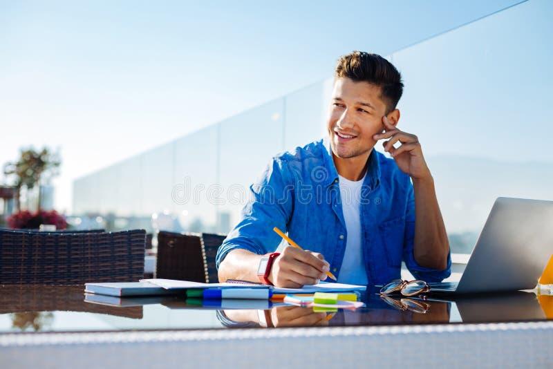 Knappe zelf - tewerkgestelde mens die terwijl het werken in koffie dromen stock foto
