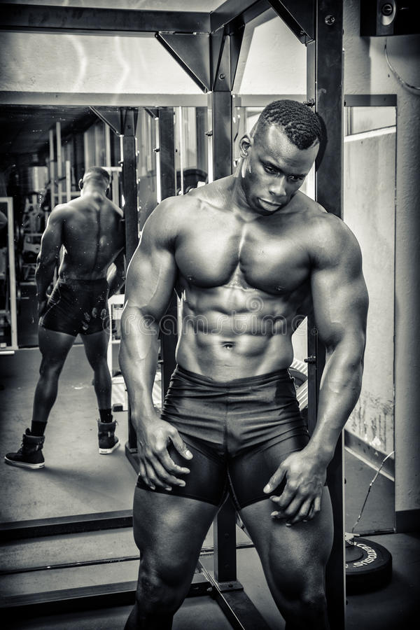Knappe zwarte mannelijke bodybuilder die na training in gymnastiek rust stock foto