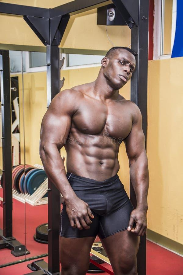 Knappe zwarte mannelijke bodybuilder die na training in gymnastiek rust royalty-vrije stock fotografie