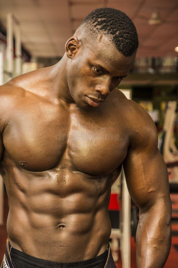 Knappe zwarte mannelijke bodybuilder die na training in gymnastiek rust stock foto's
