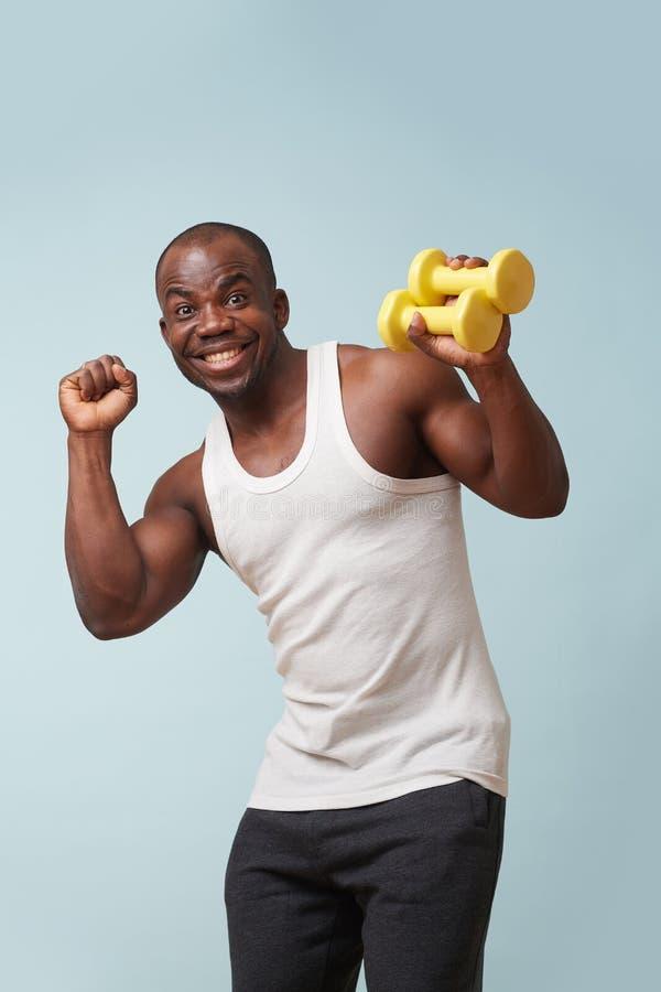 Knappe zwarte mens na training, die grappige gezichten maken Lichtblauwe achtergrond stock afbeeldingen