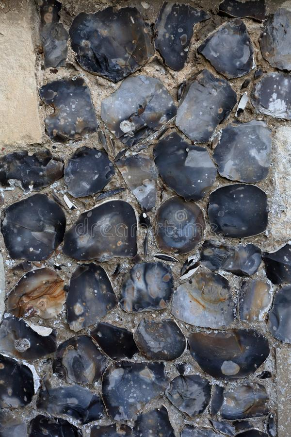 Knapped flint wall background. A flint wall in East Anglia, England. Flint, a variety of chert, has been used as a building material since Roman times stock image